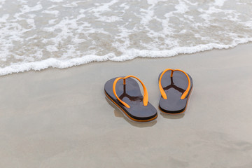 Brown and orange beach slippers soak with waving ocean, summer vacation concept.