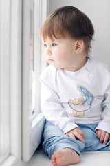 Adorable little baby seating on windowsill. looking out the window