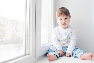 Adorable little baby seating on windowsill. look at the camera