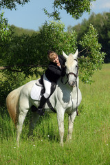 Girl in English riding clothes caress white purebred Arabian stallion