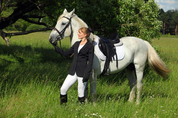 White purebred horse and blonde woman portrait, English riding clothes