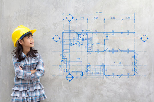 building, childhood, developing, construction and architecture concept - smiling little girl in yellow helmet showing blueprint drawing on wall