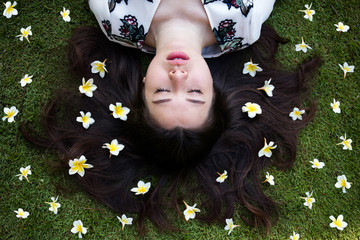 Asian beautiful young woman lying on lawn with flowers