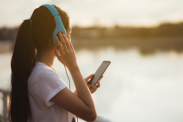 Asian woman listening music at the park with a pond during the evening.