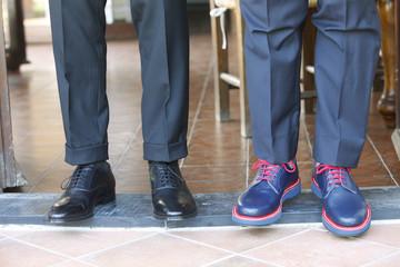 dettaglio scarpe di due uomini vestiti in maniera completamente diversa