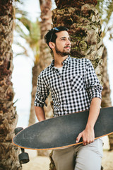 Young smiling man with skateboard leaning on palm tree.