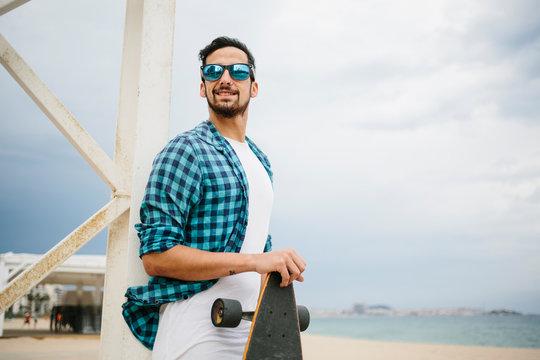 Man with skateboard at beach