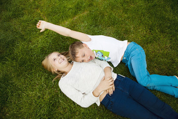 High angle view of happy siblings lying on grass