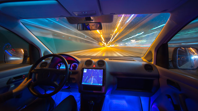 The man drive with a navigation on the rain highway. Inside view