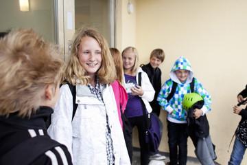 Happy friends standing in school building
