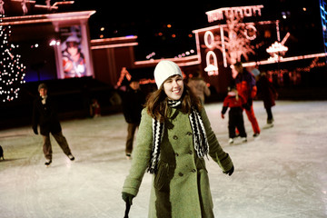 Happy woman with people doing ice-skating at night