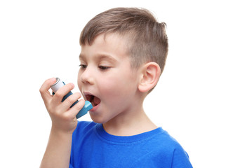 Little boy using asthma inhaler on white background
