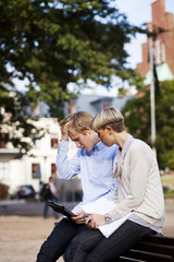 Worried friends using digital tablet while sitting on bench in university campus