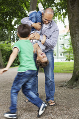 Playful father and sons enjoying at park