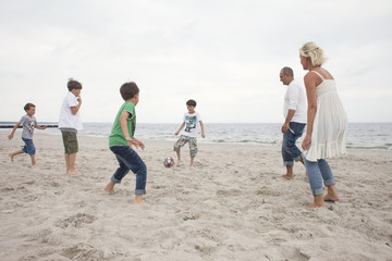 Family playing soccer at beach against sky