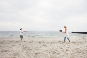 Mother and son playing at beach against sky