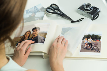 Looking at family wedding photo album. Young female engaged or married personturns pages and selects images for photoalbum