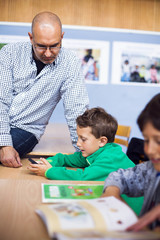 Teacher looking at boy using smart phone in classroom
