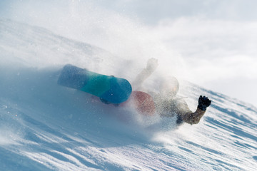 snowboarder is riding from snow hill and fall down