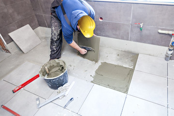 Tiling Floor & Wall. The tiler builder arranges the bathroom ceramics.  Laying tiles on the floor