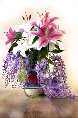 Il vaso con i fiori di giglio e il glicine