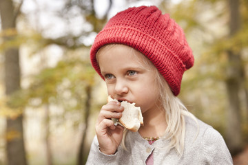 Girl eating bread outdoors