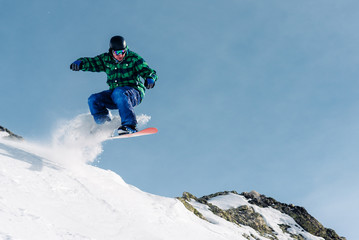 snowboarder is riding and jump from snow hill