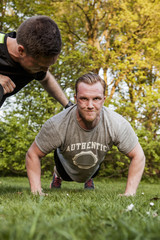 Man motivating friend doing push-ups at park