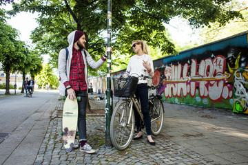 Friends with bicycle and skateboard talking on sidewalk in city