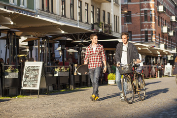Full length of male friends with skateboard and bicycles walking on city street