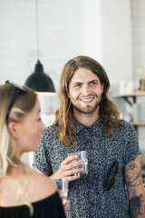 Happy young man holding drinking glass while standing with woman in restaurant