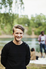 Portrait of happy man at forest with friends in background