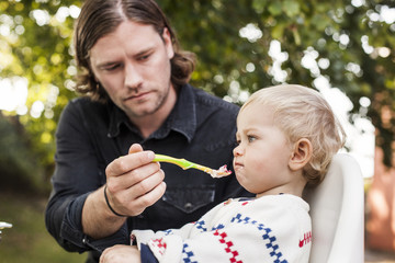 Young father feeding baby girl at park