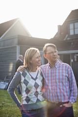 Man standing with arm around woman against house on sunny day