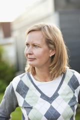 Close-up of thoughtful woman looking away while standing in back yard