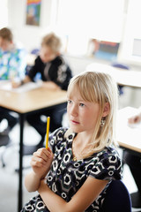 Girl sitting with pencil on in classroom