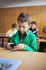 Boy using mobile phone while sitting in classroom