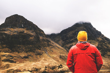 Man standing in cloudy mountains in Glencoe, Scotland.