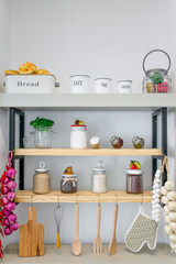 Kitchen shelves with various food ingredients and utensils.