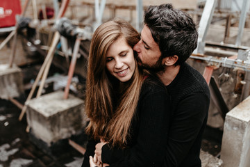 Man kissing girlfriend ear from behind