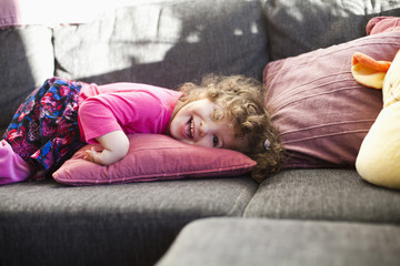 Portrait of cheerful girl lying on sofa at home