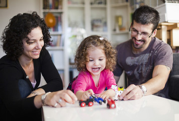 Happy family playing with toys in living room at home