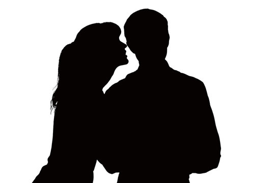 Silhouette of a woman whispers in the ear of beloved man