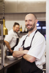 Portrait of happy chef standing arms crossed at commercial kitchen