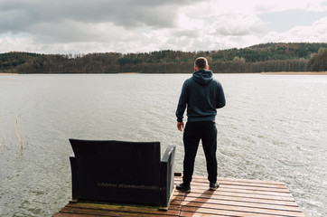 Man is standing on a pier and looking at a lake