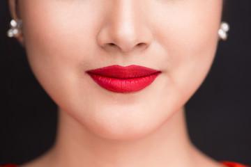 Beauty. Close up view of beautiful woman lips with red matt lipstick