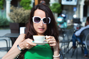 Beautiful girl with a Cup of coffee in a street cafe