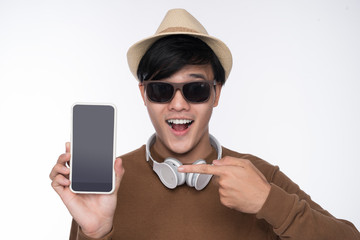 Smart casual asian man seated on chair, showing smartphone screen in studio background