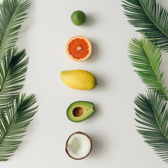 Creative layout made of summer tropical fruits and leaves. Flat lay. Food concept.