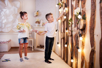 Little boy and girl play LED bulbs. They are holding light bulbs